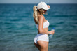 Slim girl in white sportswear with bottle of water standing outdoors on the beach, close up back view