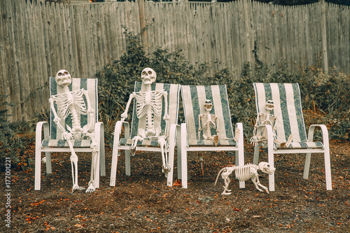 Family Of Skeletons Sits On Deck Chairs Near The House Two Skeletons Of Adults Two Skeletons For Children And A Skeleton Of A Dog Outside Buy This Stock Photo And Explore