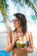 Young Woman with Sunglasses Drinking Coconut on the Tropical Beach