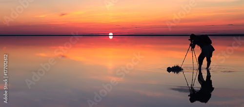 Silhouette of alone man takes a picture of a vibrant sunset reflected in shallow waters of solt lake. Banner size