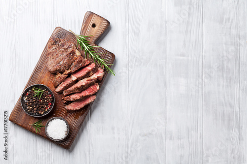 Tuinposter Grill / Barbecue Grilled beef steak with spices on cutting board