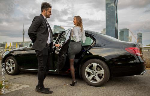 Photo  Handsome man holding car door for beautiful businesswoman