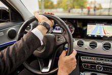 Closeup Of Man Driving A Car Holding Steering Wheel