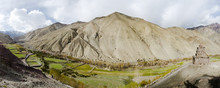 Panorama Of Stock La Valley In Ladak, Jammu And Kashmir, India, With Buddhist Shrine Looking Over A Green Farming Fields And Mountains.
