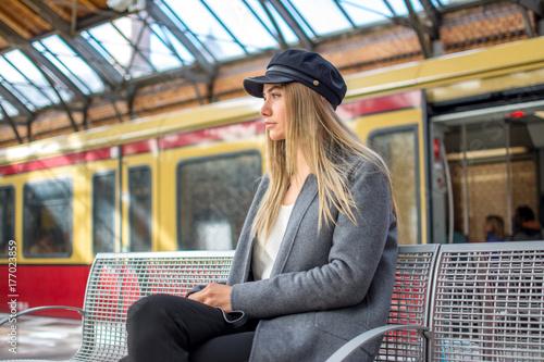 Plakat Młoda kobieta czeka na pociąg na peron na stacji kolejowej.
