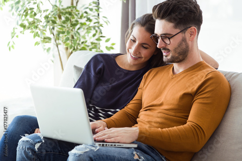 Fotografia  Beautiful young couple using laptop on the sofa at home.