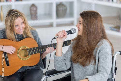 Zdjęcie XXL młoda kobieta ze śpiewem, podczas gdy jej przyjaciółka gra na gitarze