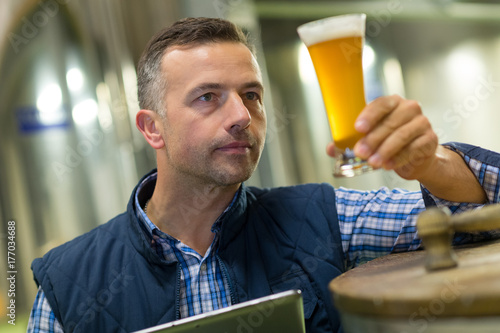 Fototapety, obrazy: handsome brewer in uniform tasting beer at the brewery
