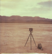 Large Format Camera On A Tripod With A Bag Sitting In The Middle Of The Desert