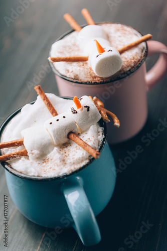 a mug with hot chocolate on a wooden table with a marshmallow man who is resting in a mug