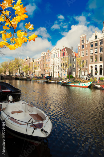 Photo  Boats and old Houses over canal water, Amsterdam, Netherlands at autumn day
