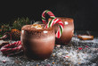 Traditional Christmas drinks. North Pole Cocktail with candy cane sweets, peppermint, hot chocolate or cocoa, ginger ad milk. Dark background, with Christmas decoration, copy space