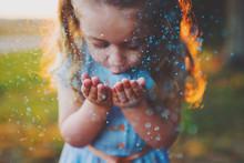 Girl Blowing Blue Glitter Outdoors