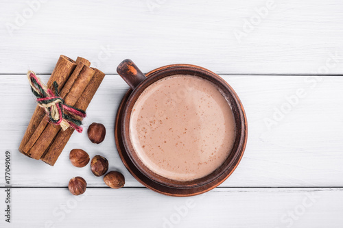 Staande foto Chocolade Hot cocoa with milk in brown clay cup, hazelnut and cinnamon sticks on table of white wooden planks, top view