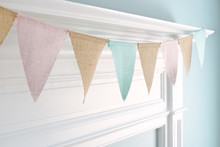 Close-up Of A White Mantel Decorated With Pastel Flag Bunting.