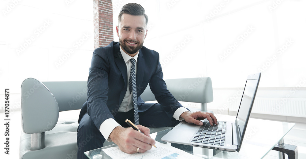 Fototapeta Businessman working with business graphics on a laptop computer