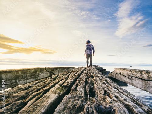 Traveler posing on ruined pier