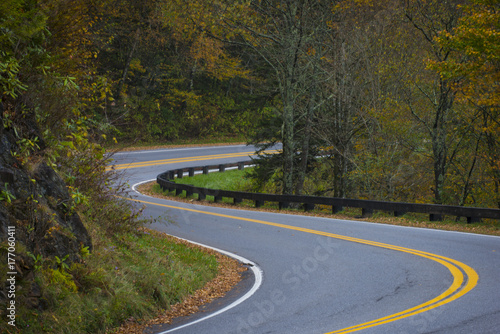 Fotografie, Obraz  Twisting curvy road winding through fall colorful trees in national park with lo
