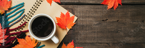 Fotografia Autumn leaves and a cup of coffee with plaid on old vintage wooden background