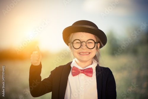 afb07f1a95c Outdoor portrait of funny little girl in bow tie and bowler hat showing  thumb up. Retro stile.