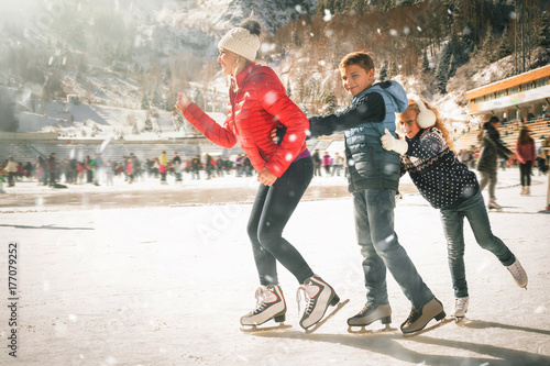 Photo Happy family outdoor ice skating at rink. Winter activities
