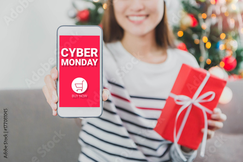 young beautiful asian woman hands holding gift box and smartphone with cyber monday screensmile