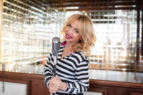 Plakat Piękna kobieta, blondynka, mikrofon. śpiewanie, piękny uśmiech