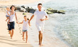 Young family of four running on sandy beach