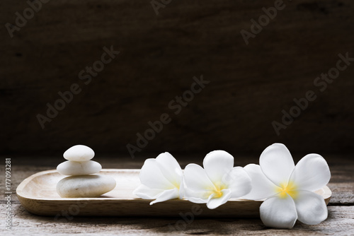 Beautiful plumeria or temple,spa flower with white zen stones on rustic wood background