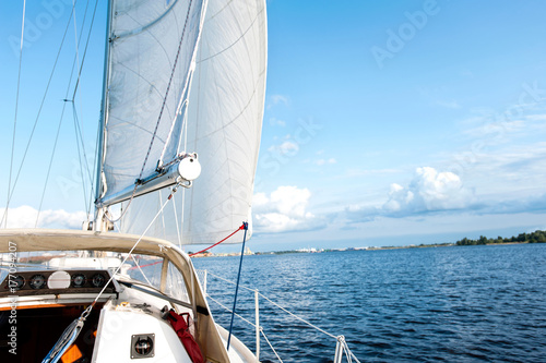 Poster Zeilen White yacht drifts in sunlight on blue cloudy sky background.
