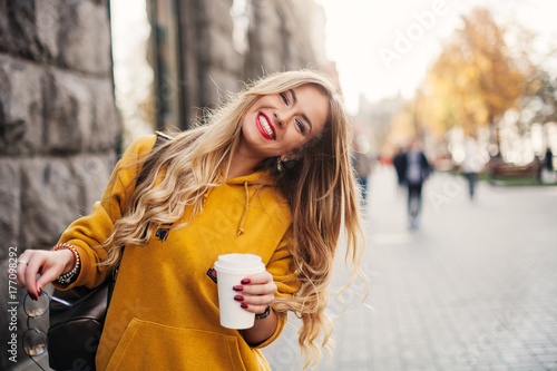 Fototapeta Stylish happy young woman wearing boyfrend jeans, white sneakers bright yellow sweetshot