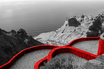 Fototapeta Czarno-Białe Fortified red wall of the medieval castle. Beautiful scenic view of the country house on the mountain and the blue sea. Panoramic sea view. Black and white, red