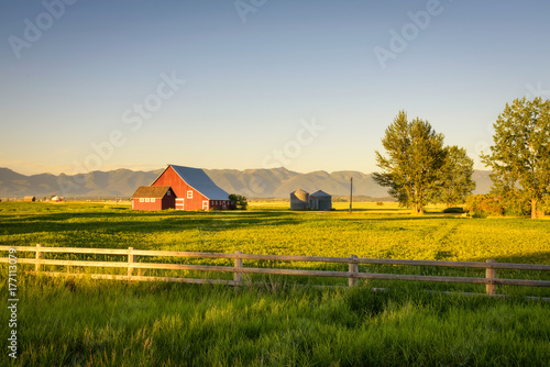 Fotografiet  Summer sunset with a red barn in rural Montana and Rocky Mountains
