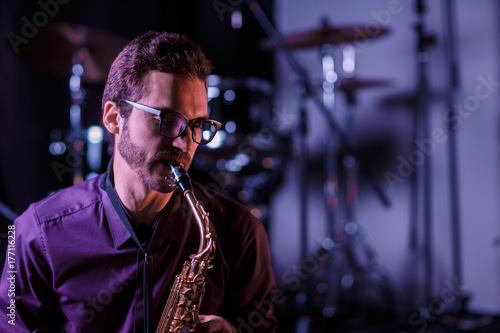Zdjęcie XXL Zamyka w górę portreta saksofonowy gracz z bębenami na tle