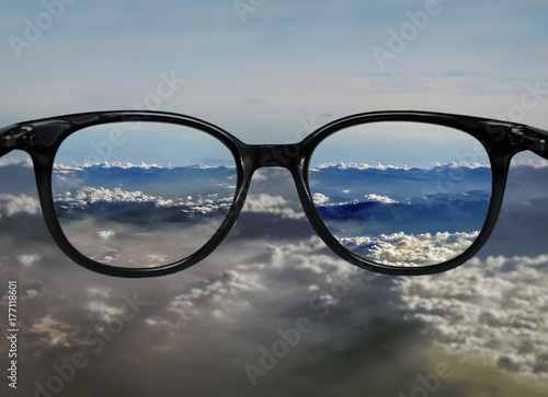 Fotografie, Obraz  Clear vision through glasses on blue clouds landscape
