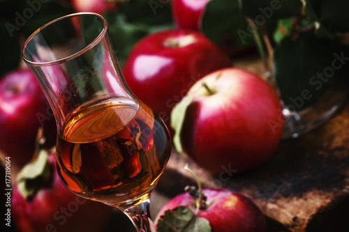 French strong golden alcoholic drink from apples, vintage wooden background, selective focus