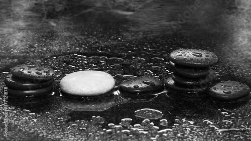Obraz na płótnie Zdrojów kamienie na ciemnym tle z wodą opuszczają i odbicie