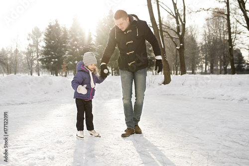Father and daughter ice skating on frozen lake