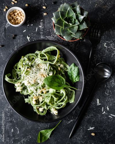 Fotografía  Green spinach pasta with cheese and pine nuts in black bowl with black cutlery on dark stone table