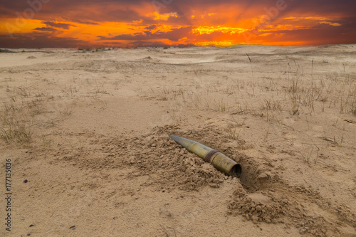 Poster de jardin Desert de sable old artillery metal projectile on the sand in the desert