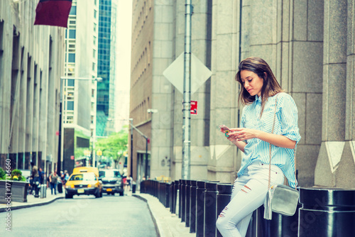 Fotografie, Tablou  Young Argentine Woman wearing light blue striped shirt, white destroyed jeans, shoulder carrying small bag, sitting on street in New York, looking down, texting on cell phone