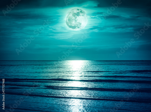 Poster Mer / Ocean Colorful sky with dark cloud and bright full moon over seascape.