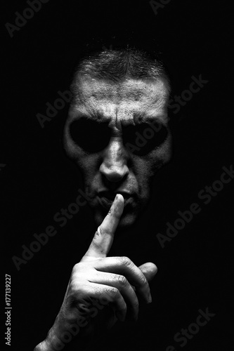 Fototapeta Angry mature man with an aggressive look making the silence sign in a threatening and creepy way