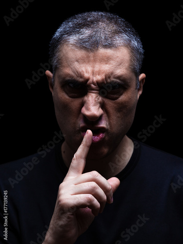 Photo Furious mature man with an aggressive look making the silence sign in a violent and threatening way