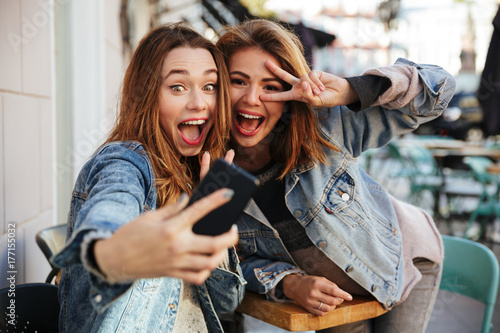Fotografie, Obraz  Two emotional female friends in jeans jackets posing while making selfie in city