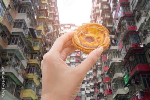 Photo  hand holding egg tart with old apartment in hongkong
