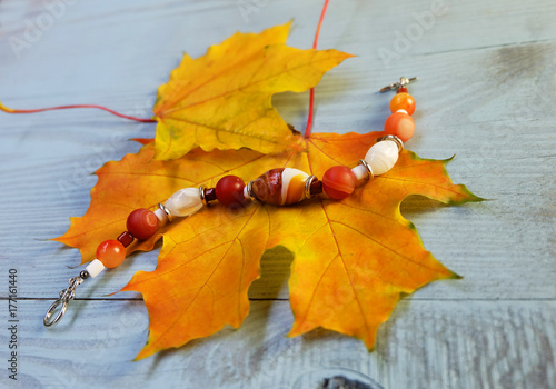 Fotografie, Tablou  Bracelet made of Murano glass and carnelian on a background of autumn leaves on a blue wooden table