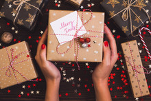 Woman Hands Holding Christmas Holiday Gift Box With Postcard Merry Xmas On Decorated Festive Table