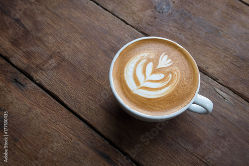 Fotografie, Obraz  A white cup of hot latte art coffee on the wooden table in coffee shop