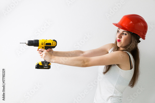 Fotografía  Funny woman using power driil for work at home